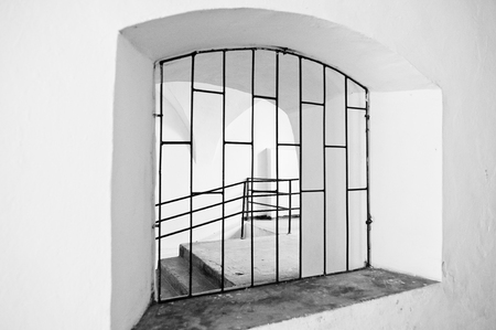 lockup: Arched window with metal grating. Black and white Stock Photo