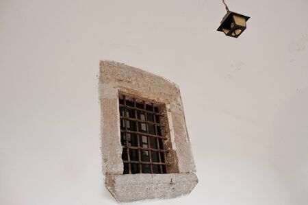 lockup: Old stone window with metal grating and chandelier