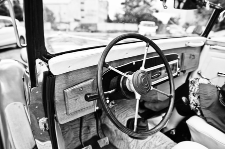 gearstick: Wooden interior and steering wheel on old vintage retro car. Black and white photo