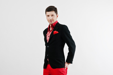 red pants: Fashion young man in black suit and red pants casual poses at studio Stock Photo