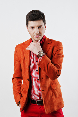red pants: Fashion young man in orange suit and red pants casual poses at studio