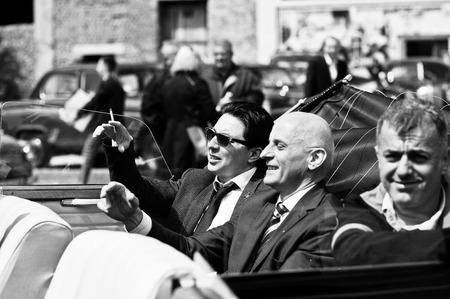 ray ban: Podol, Ukraine - May 19, 2016: Elegant man on sunglasses Ray Ban with cigarette sitting on Maybach Cabriolet, luxury classic car. Black and white photo