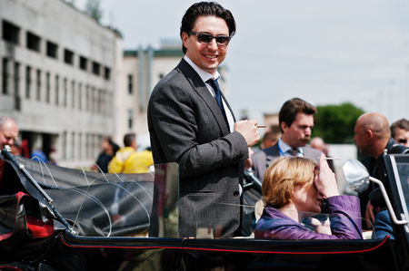 ray ban: Podol, Ukraine - May 19, 2016: Elegant man on sunglasses Ray Ban with cigarette stay and smile on Maybach Cabriolet, luxury classic car.
