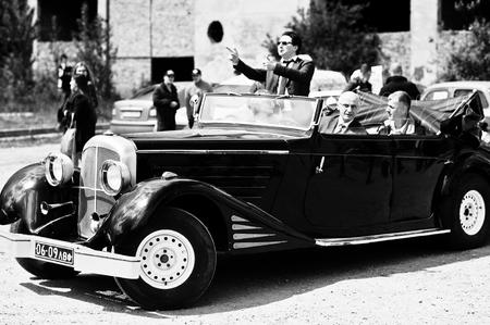 Podol, Ucraina - 19 Maggio, 2016: Uomo elegante in occhiali da sole Ray Ban con soggiorno sigaretta e sorridere su Maybach Cabriolet, auto d'epoca di lusso. Foto in bianco e nero