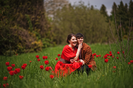 red tulip: Couple hugging in love at red tulip field. Stylish man at velvet jacket and girl in red dress in love together