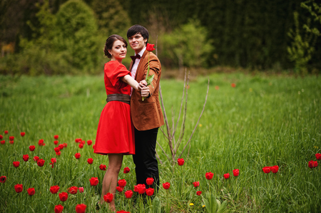 velvet dress: Couple hugging in love at red tulip field. Stylish man at velvet jacket and girl in red dress in love together