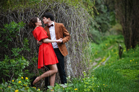 velvet dress: Couple hugging in love background dry branches at field. Stylish man at velvet jacket and girl in red dress in love together Stock Photo