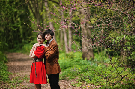 velvet dress: Couple hugging at forest with spring branches. Stylish man at velvet jacket and girl in red dress in love together Stock Photo