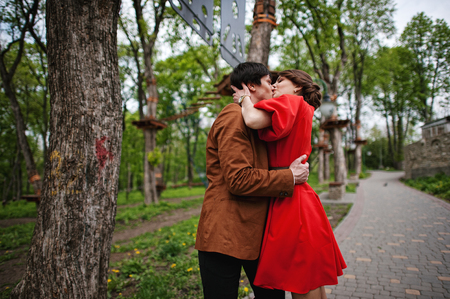 velvet dress: Happy couple passionate kissing at green park. Stylish man at velvet jacket and girl in red dress in love together