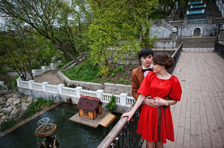velvet dress: Couple hugging in love background bridge of river with fountain. Stylish man at velvet jacket and girl in red dress in love together