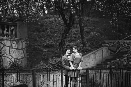 red barrier velvet: Couple hugging in love background barrier of cliff. Stylish man at velvet jacket and girl in red dress in love together. Black and white photo Stock Photo