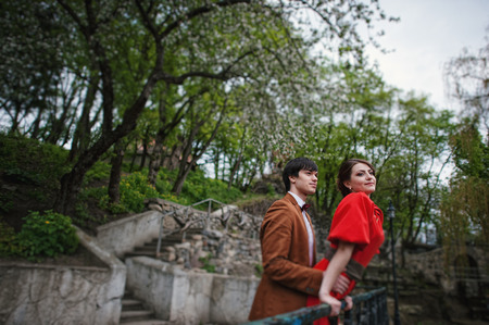 red barrier velvet: Couple hugging in love background barrier of cliff. Stylish man at velvet jacket and girl in red dress in love together