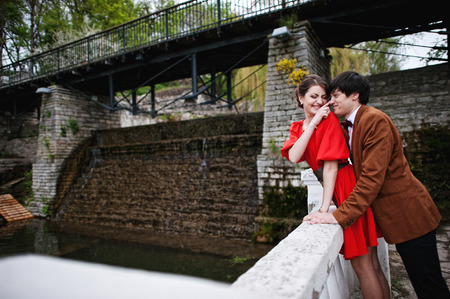 happy family nature: Couple hugging in love background water dam. Stylish man at velvet jacket and girl in red dress in love together
