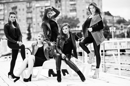 berth: Five beautiful young girls models at leather jackets posing on berth. Black and white photo