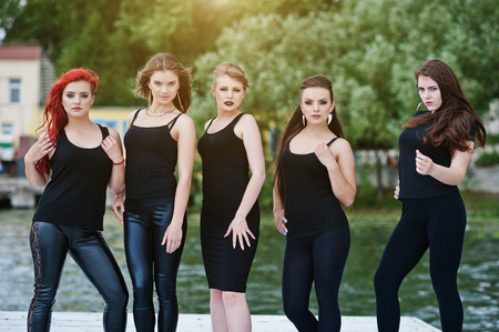 Five beautiful young sexy girls models in black tight dress posing on pier