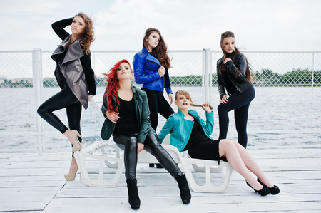 berth: Five beautiful young girls models at leather jackets posing on berth.