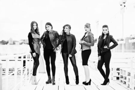 cian: Five beautiful young girls models at leather jackets posing on berth. Black and white photo