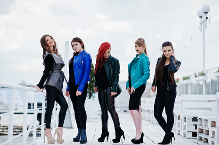 cian: Five beautiful young girls models at leather jackets posing on berth.