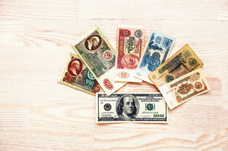 Set of bill USSR roubles money with 100 dollar on wooden background.