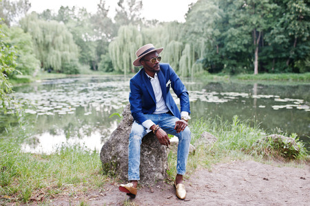 uomini belli: Ritratto di moda ricco uomo nero in giacca blu, cappello e occhiali da sole Archivio Fotografico