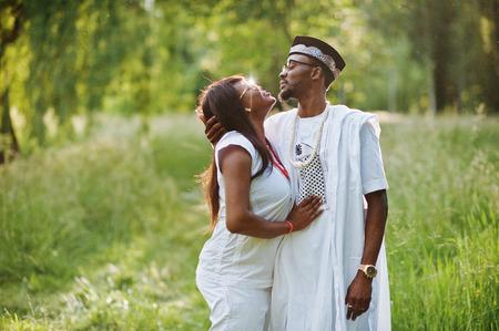 mannequin africain: Noir couple africain dans l'amour embrassant au parc de verdure sur le coucher du soleil Banque d'images