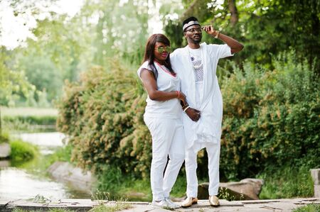 wealthy lifestyle: Rich african couple at white national dress and sunglasses