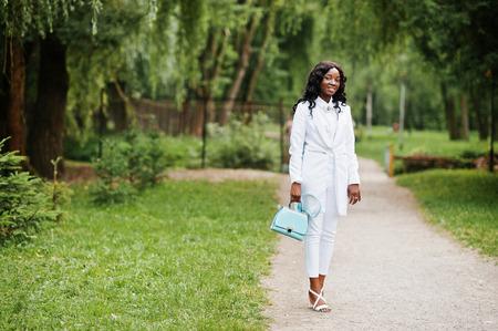 turqoise: Stylish black african american girl posing on park with turqoise bag