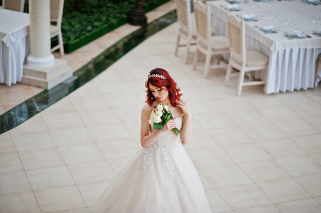lips glow: Charming red-haired bride with wedding bouquet at hand posed against the  great wedding hall with tables and chairs indoor