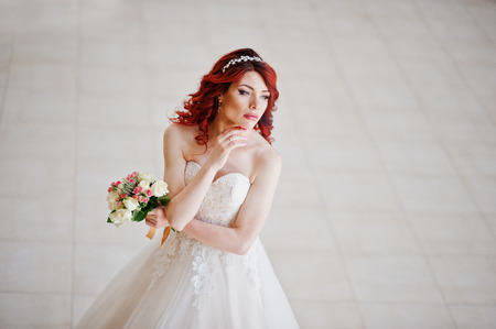 lips glow: Top view of charming red-haired bride with wedding bouquet at hand posed against wgite tile on the great wedding hall