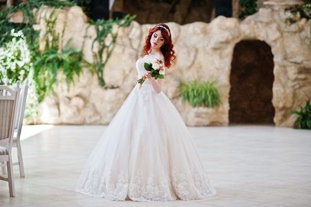 lips glow: Charming red-haired bride with wedding bouquet at hand posed at great wedding hall with caves and vegetation indoor Stock Photo