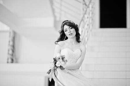 lips glow: Charming red-haired bride with wedding bouquet at hand posed on the stairs with metal railing at great wedding hall indoor. Black and white photo