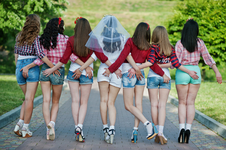 booty shorts: Back view of seven happy and sexy girls on short shorts holding hands on the buttocks and posed on road at park on bachelorette party Stock Photo
