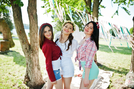 short shorts: Three cheerful beautiful girls in short shorts posed background decoration at bachelorette party
