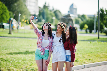 short shorts: Three girls in short shorts and wreaths on heads make selfie