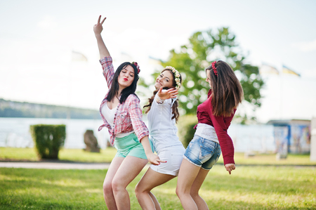 short shorts: Three happy girls in short shorts and wreaths on heads dancing and having fun on green grass at bachelorette party