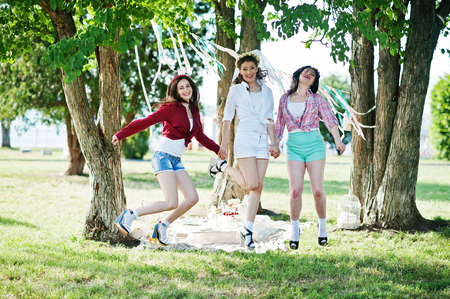 short shorts: Three cheerful beautiful girls in short shorts jumping background decoration at bachelorette party Stock Photo