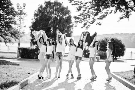 throw up: Seven happy and sexy girls on short shorts throw up shirts and having fun at park on bachelorette party Stock Photo