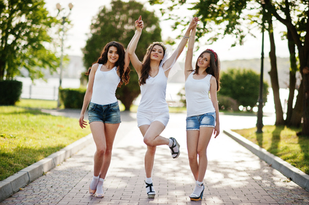 Three happy and sexy girls on short shorts and white shirts posed on road at park on bachelorette party Stock Photo