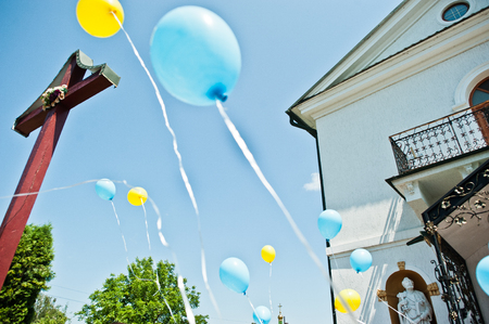 Blue and yellow balloons at sky background cross at church. Stock Photo - 59760389