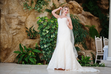 posed: Gorgeous blonde bride posed at great awesome wedding hall Stock Photo