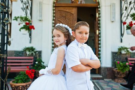 Pierwsza Komunia Święta, brat i siostra pobyt w białej sukni tle kościoła