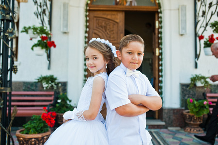 First holy communion, brother and sister stay at white dress background church