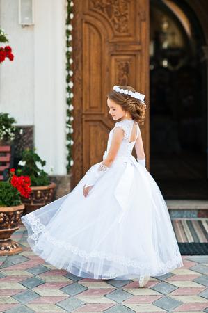 흰 드레스 및 헌화는 첫 번째 성령 성 찬 식을 교회에 대한 귀여운 소녀 초상화를 교회 게이트 스톡 콘텐츠