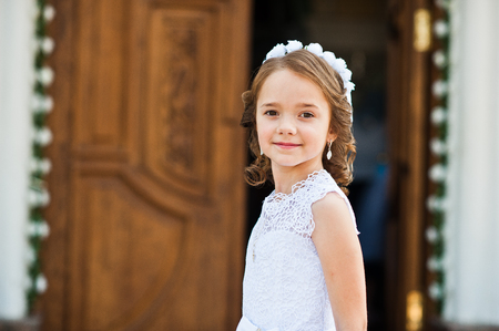 christian marriage: Portrait of cute little girl on white dress and wreath on first holy communion background church gate