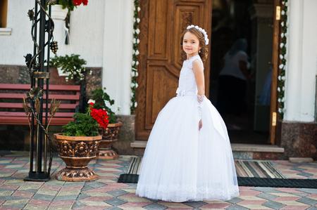 可爱的小女孩的肖像,白色的连衣裙和花环在第一圣餐堂的背景教堂大门上