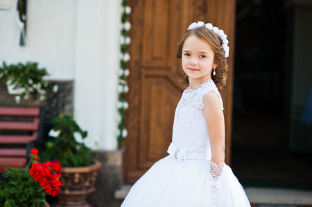 Portrait of cute little girl on white dress and wreath on first holy communion background church gate