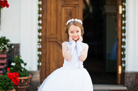 Portrait of cute little girl on white dress and wreath on first holy communion background church gate Stock Photo - 60126330