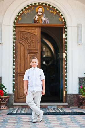 dearly: Portrait of little boy on white wear and bow tie on first holy communion background church gate Stock Photo
