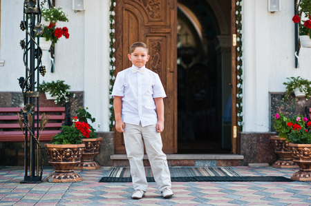 Portrait of little boy on white wear and bow tie on first holy communion background church gate Stock Photo