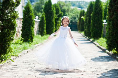 可爱的小女孩的肖像在白色的连衣裙和花环的第一圣餐的背景杜嘉巷